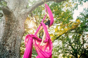 Girl practicing aerial silks hanging from tree, St. Louis, MO, I